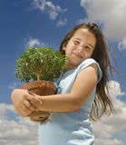 Girl holding small tree. Against cloudy blue sky Stock Images