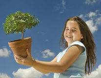 Girl holding small tree. Against cloudy blue sky Stock Photo