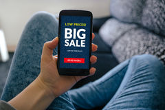 Girl holding smart phone with big sale concept on screen Royalty Free Stock Images