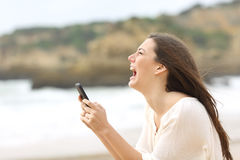 Girl holding a smart phone crying desperately Stock Photography