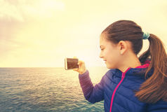 Girl holding smart phone and record sea royalty free stock image