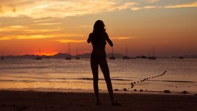 Girl holding smart phone and taking red sunset photo on the tropical beach.  Silhouette of a woman, yachts and mountains on. Background. Seascape royalty free stock image