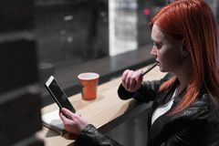 Girl holding smartphone in hand, sit in cafe, working, pen, use gadget. Network, wifi, social, communication. Freelancer works stock photos