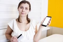 The girl is holding smartphone and plastic payment card in her hand. Online purchases in the phone stock image