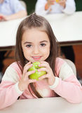 Girl Holding Smith Apple With Classmates In Stock Photos