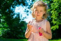 Girl holding soap bubbles Stock Photos