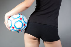 Girl holding a soccer ball showing her back Stock Photo