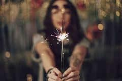 Woman hands holding sparklers. Girl holding sparklers, focus on hands and sparklers, blurry background with lights Royalty Free Stock Image