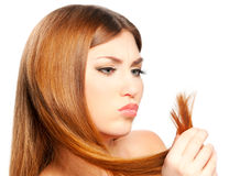 Girl holding split ends. Beautiful woman holding split ends of her hair and frown Stock Photography