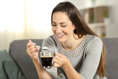 Girl holding a spoon with sugar and a coffee cup Royalty Free Stock Photo
