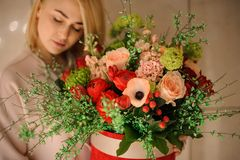 Girl holding a spring bouquet of tender peach color and passion red flowers. Decorated with green leaves and berries royalty free stock image