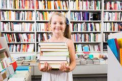 Girl holding a stack of books in a bookstore Stock Photos