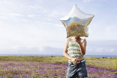 Girl Holding Star Shaped Balloon In Front Of Face At Flower Fiel Royalty Free Stock Photography