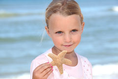 Girl holding a starfish Royalty Free Stock Photo