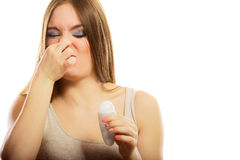 Girl holding stick deodorant in hand. Daily skin care and hygiene. Funny girl covers her nose sweating, using stick deodorant. Young woman holding antiperspirant Stock Photography