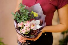 Girl holding a stylish bouquet of roses, orchid, eucalyptus Royalty Free Stock Photography