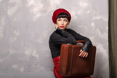 Girl holding a suitcase. Portrait of a romantic Frenchwoman beret. A girl holding a suitcase. Travel concept Royalty Free Stock Photos