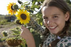 Girl (9-11) holding sunflowers growing in garden, smiling, side view, close-up, portrait Stock Image