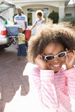 Girl (8-10) holding sunglasses to face in driveway, smiling Royalty Free Stock Photography