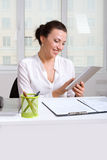 Girl holding a a tablet browsing news smiling Royalty Free Stock Image