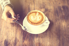 Girl holding a teaspoon and cup of cappuccino on a wooden table Royalty Free Stock Photo