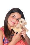 Girl holding teddy bear. A young girl holds and cuddles with a soft, stuffed teddy bear Royalty Free Stock Photo