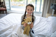 Girl holding teddy bear on bed in bedroom. Portrait of girl holding teddy bear on bed in bedroom Stock Image