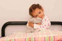 Girl holding teddy in bed Royalty Free Stock Photo