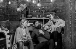 Girl holding teddy enjoys evening with parents. Bearded man sitting between his wife and child in countryside house royalty free stock images