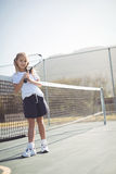 Girl holding tennis racket while sitting by net Royalty Free Stock Image