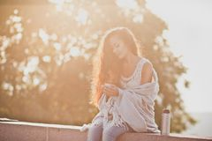 Girl holding a thermos with steaming tea. Girl wrapped in a blanket holding a thermos with steaming tea during sunrise Stock Images