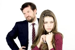 Girl holding tight her cell phone while father is angry Stock Image