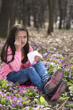 Girl holding tissue and rubbing eyes sitting on the ground Stock Photos