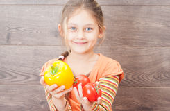 Girl holding a tomato on a wooden background Royalty Free Stock Image