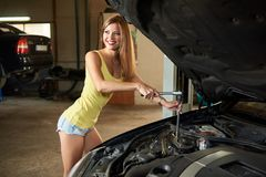 Girl is holding tools while repairing car with open hood. A girl is holding tools while repairing a car with an open hood in the garage. The girl with a dazzling Stock Photo