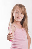 Girl holding toothbrush forward against a white background Stock Photos