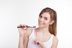 Girl holding a toothbrush smiles Stock Photo