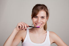 Girl holding a toothbrush smiles Stock Images