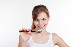 Girl holding a toothbrush smiles Stock Photography