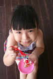 Girl holding toy cake. Girl sitting on the floor holding toy cake Stock Image