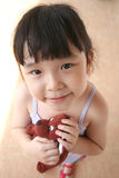 Girl holding toy dog. Little girl smiling & holding brown toy doy royalty free stock image