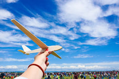 Girl holding toy plane at an airshow with crowd in the backgroun Royalty Free Stock Photos