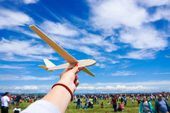 Girl holding toy plane at an airshow with crowd in the backgroun Royalty Free Stock Photo