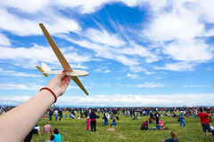 Girl holding toy wood plane at an airshow with crowd in the back Stock Images