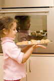 Girl holding tray of cookies to bake. In front of oven Royalty Free Stock Photo