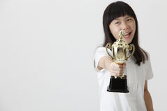Girl holding trophy. Chinese girl holding trophy and the focus on trophy royalty free stock photo