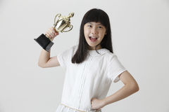 Girl holding trophy. Chinese girl happy to own a trophy royalty free stock photo