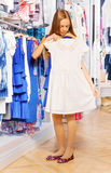Girl holding and trying white dress on hanger Royalty Free Stock Photos