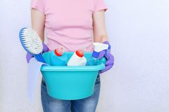 The girl is holding a turquoise plastic basin with cleaning supplies for cleaning stock photography