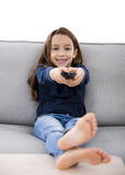 Girl holding a TV remote Royalty Free Stock Images